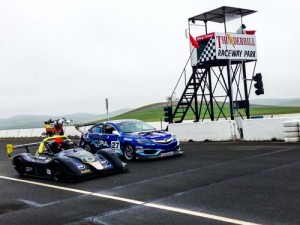 A Radical sports racer and Acura ILX sit on the race grid